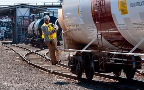 Image of rail switch operator riding tank car in railyard